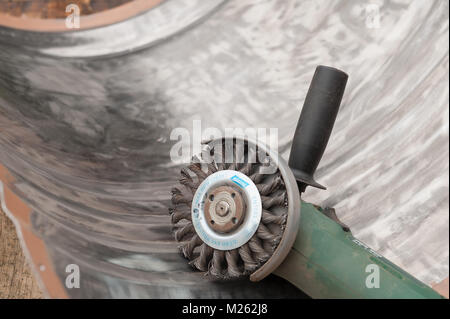 Bare steel exposed on the inside of a 205l oil drum worn of with angle grinder and twisted steel brush wheel, knot - Stock Photo