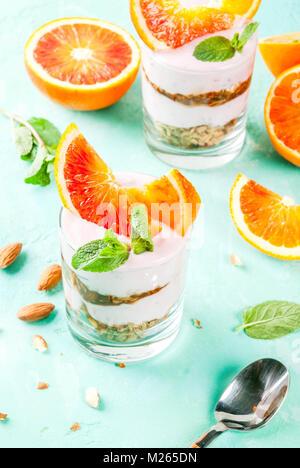 Healthy breakfast, Blood Orange Parfait with granola. yogurt, almond and mint, light blue background, copy space - Stock Photo