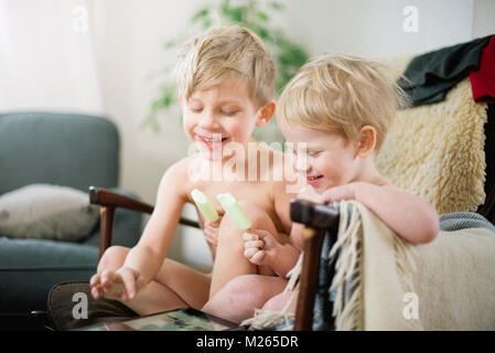 Two brothers eating ice cream in the recliner while enjoying Internet movie clips on the tablet. - Stock Photo