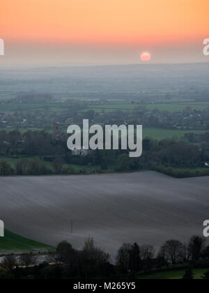 Sunset casts a red sky through haze over the farmland landscape and scattered villages of the Aylesbury Vale in - Stock Photo