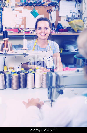 smiling young professional female tailor using sewing machine at workshop - Stock Photo