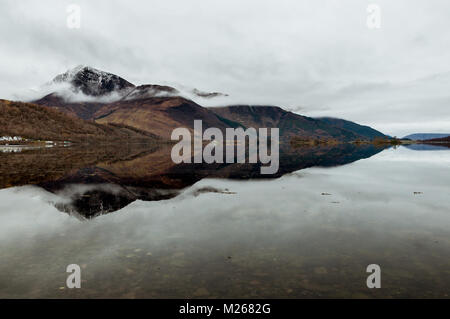 Beinn a'Bheithir reflected in Loch Leven on a cold, grey morning in March, from Invercoe near Glencoe, Scotland. - Stock Photo