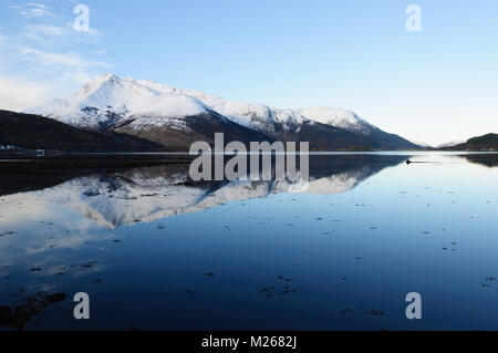 Beinn a'Bheithir reflected in Loch Leven on a cold, bright, still March morning, from Invercoe near Glencoe, Scotland. - Stock Photo