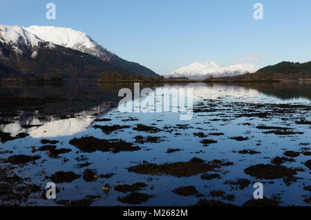 Beinn a'Bheithir, above Ballachulish, and the distant hills of Ardgour reflected in Loch Leven on a cold, bright, - Stock Photo