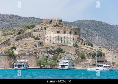 Venetian fortifications and cruise boats, Spinalonga (Kalydon) Island, Elounda, Lasithi Region, Crete (Kriti), Greece - Stock Photo