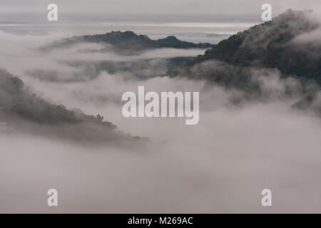 Amazing landscape scene above the clouds of mist between the mountains peaks and hills at sunset, Heping District, - Stock Photo