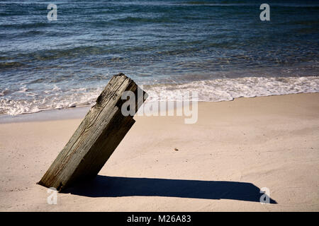 Timber embedded in the sand on a beach - Stock Photo