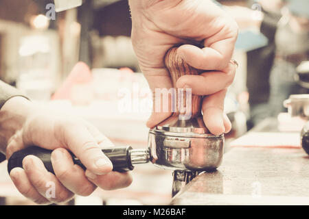 Barista presses ground coffee using tamper. Shallow depth of field, pastel color toning - Stock Photo