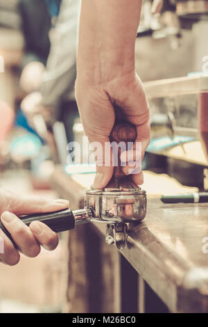 Female barista presses ground coffee using tamper. Shallow depth of field, pastel color toning - Stock Photo