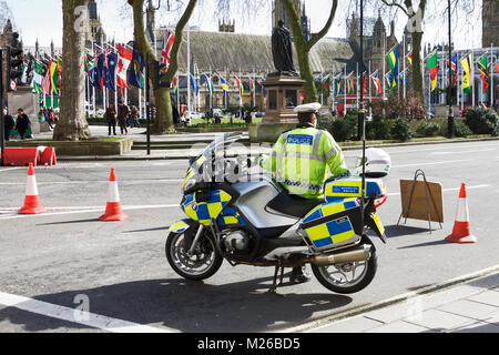 Metropolitan Police Motorcyclist, Parliament Square, London, UK. Commonwealth Day London. Commonwealth flags London. - Stock Photo
