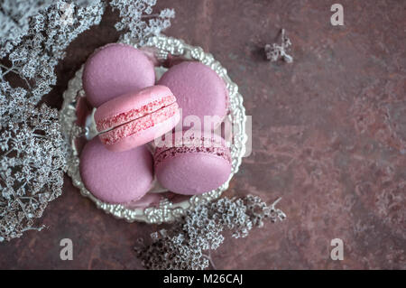 Freshly baked macaroons in a wicker basket on a wooden background. Selective focus. - Stock Photo
