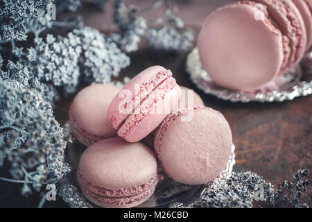 Freshly baked macaroons on metal plate with small white flowers on wooden background. Selective focus. - Stock Photo