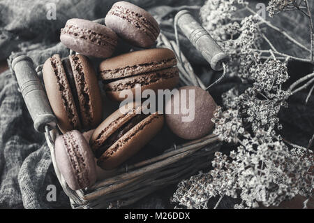 Freshly baked macaroons in wicker basket with handles with small white flowers on wooden background. - Stock Photo