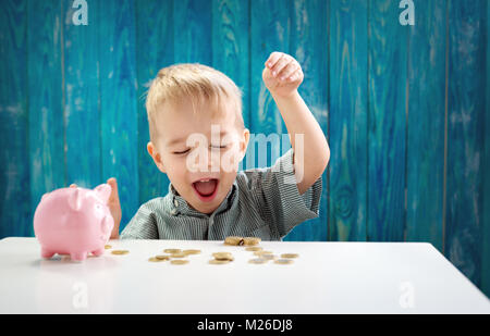 two years old child sitting on the floor and putting a coin into a piggybank - Stock Photo
