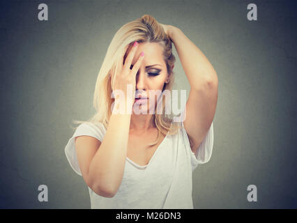 Young casual blonde rubbing forehead suffering from head pain. - Stock Photo