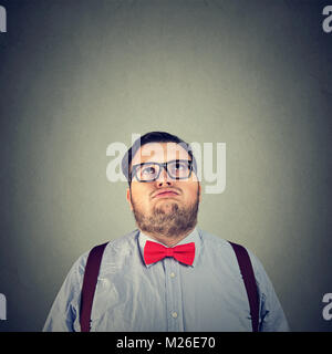 Young chubby man in bow tie looking up in boredom posing on gray background. - Stock Photo