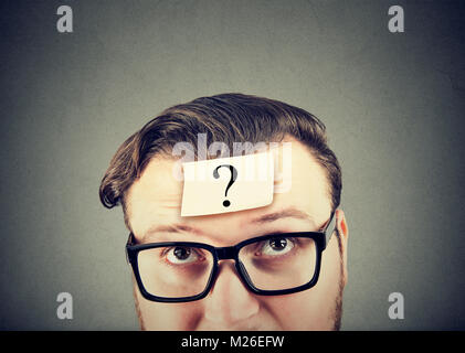 Young man in eyeglasses having question in mind looking perplexed. - Stock Photo