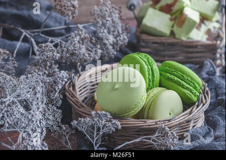 Freshly baked colored macaroons in wicker basket with handles with small white flowers on wooden background. - Stock Photo