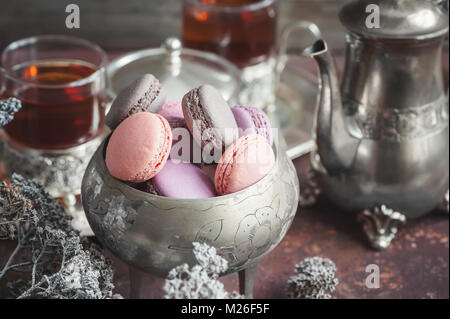 Freshly baked macaroons on metal plate with small white flowers and tea appliances composition on wooden background. - Stock Photo