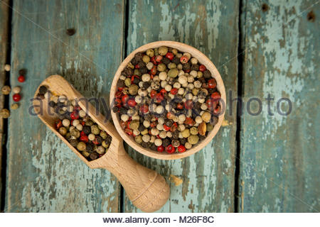Mixed peppercorns in a wooden bowl - Stock Photo