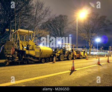 A raft of heavy road laying machine equipment on the side of the road at night in the suburbs of Edinburgh in winter. - Stock Photo