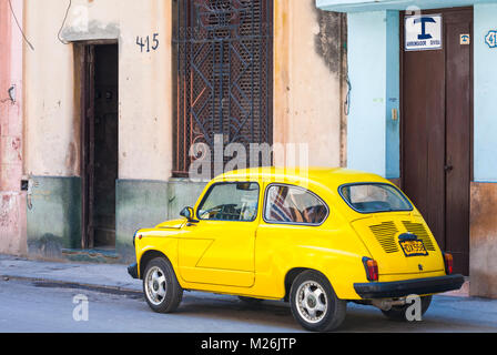 Yellow Fiat car parked in road at Havana, Cuba, West Indies, Caribbean, Central America - Stock Photo