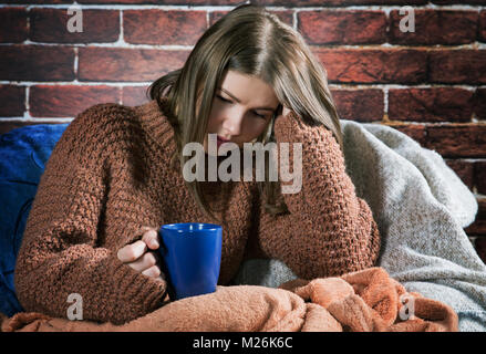 girl with a cup of tea sits wrapped in a rug - Stock Photo