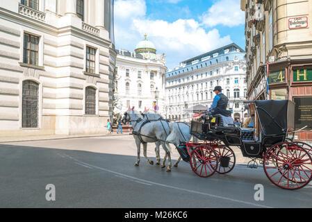 Austria, Vienna,  Hofburg area, tourists ride horse drawn carriage in Michaelerplatz - Stock Photo