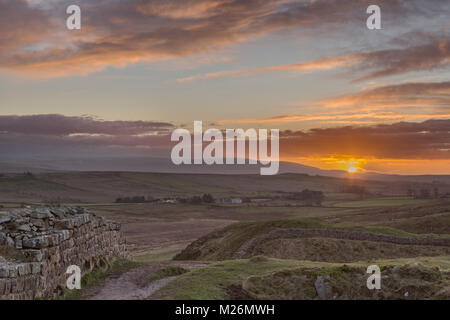 Hadrian's Wall: a winter view to the west, looking over Sycamore Gap (between Highshield and Peel Crags) at sunset, - Stock Photo
