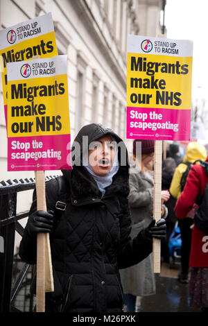 Demonstration called by the People's Assembly in support of the NHS. A woman holds two placards saying 'Migrants make our NHS'