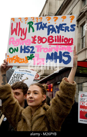 Demonstration called by the People's Assembly in support of the NHS . A placard asks  why tax payers are paying £80 billion for HS2 trainline.
