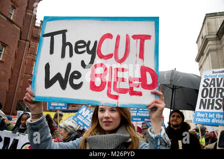 Demonstration called by the People's Assembly in support of the NHS (National Health Service}. A young woman holds a placard saying 'They cut we bleed'
