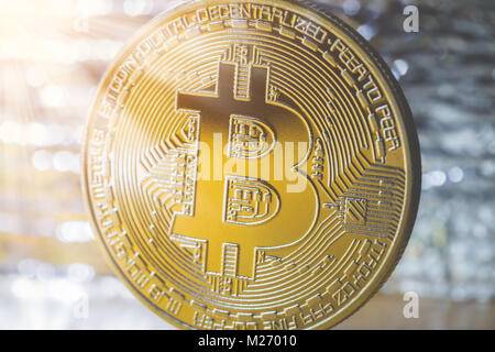 Golden Bitcoin in a ray of light on a silver background. Close up - Stock Photo