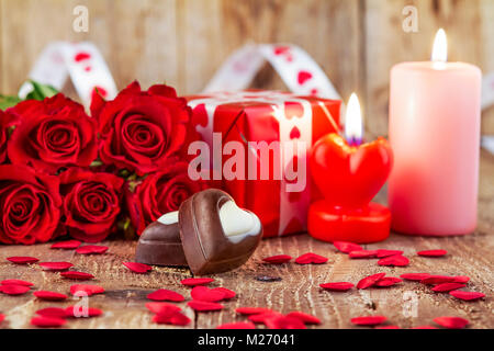 Chocolate pralines in front of bouquet of red roses and candles on wooden background. Valentines day concept. Mother's - Stock Photo