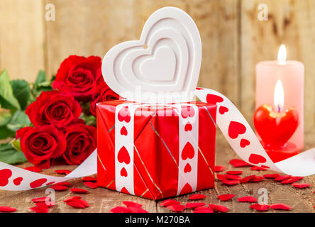 Shape of white heart over gift box in front of bouquet of red roses and candles on wooden background. Valentines - Stock Photo