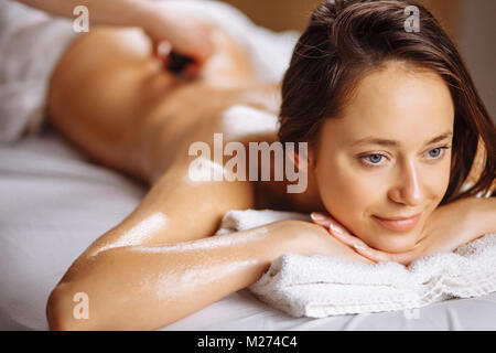 young Woman getting hot stone massage at spa salon - Stock Photo