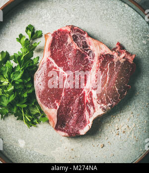 Flat-lay of raw uncooked dry-aged t-bone prime beef steak - Stock Photo