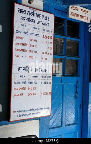 Station timetable for the Kalka to Shimla narrow gauge railway, India - Stock Photo