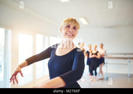 Smiling senior woman taking ballet lessons in a dance studio with a group of friends in the background - Stock Photo