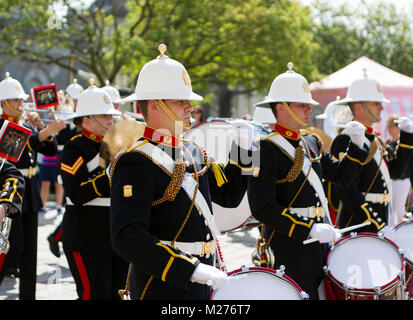 The Band of HM Royal Marines march through Plymouth's Royal William Yard on a bright sunny day. - Stock Photo