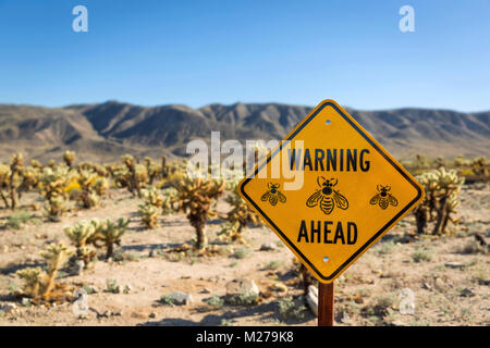 Bee Warning Sign in front of Cholla Cactus Garden in Joshua Treen National Park, California - Stock Photo
