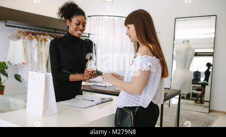 Customer shopping designer wear at a fashion boutique. Customer making payment using a credit card on a point of - Stock Photo