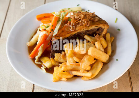 Steak and ale pie served with chips. The dish is a popular British pub meal. - Stock Photo