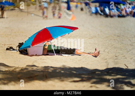 Man at the beach taking a nap in the shade - Stock Photo