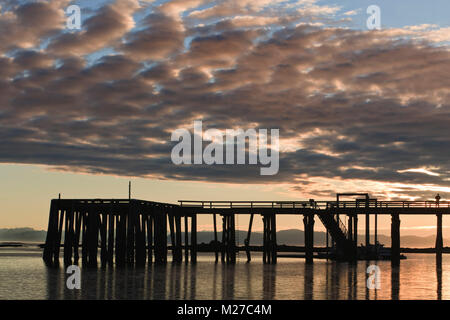 The dock at Kake, Kupreanof Island, in the Inside Passage of Southeast Alaska, in silhouette at sunset. - Stock Photo