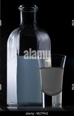 bank of moonshine and a glass on a black background - Stock Photo