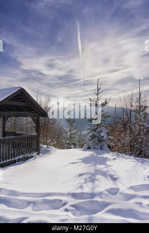Wooden bower near mountain trail. Winter sunny day and hazy mountain in the background. Kremnica Mountains, Slovakia, - Stock Photo