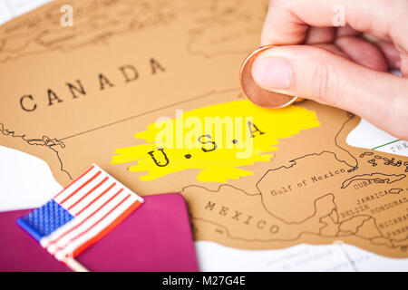 Travel holiday to United States of America concept with passport and flag with female hand scratching map choosing - Stock Photo