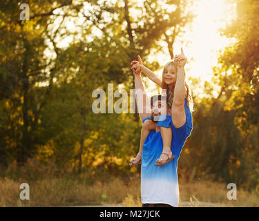 Family time. The father holds the daughter on the shoulders of piggyback. He supports the little girl by the hand. - Stock Photo
