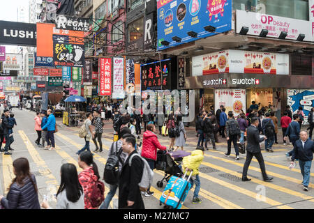 Hong Kong - January 25 2018: People crossing a busy street in the very crowded Mong Kok shopping district in Kowloon, - Stock Photo